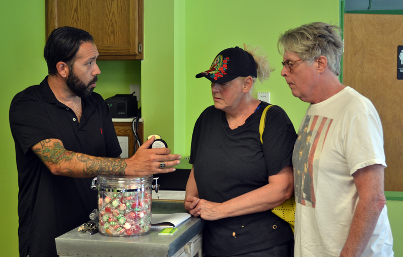 Downeast Medicinals co-owner David Boucher (left) shows Elaine and Ralph Bryant a cannabidiol body lotion for sale at the Edgecomb business Monday, Aug. 21. (Abigail Adams photo)