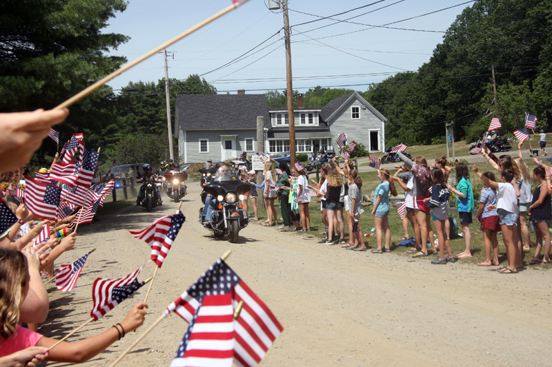 Campers wave American flags to welcome veterans to the Burgers, Bikes & Rods rally at Wavus Camps in Jefferson on Saturday, July 29. (Photo courtesy Russ Williams)