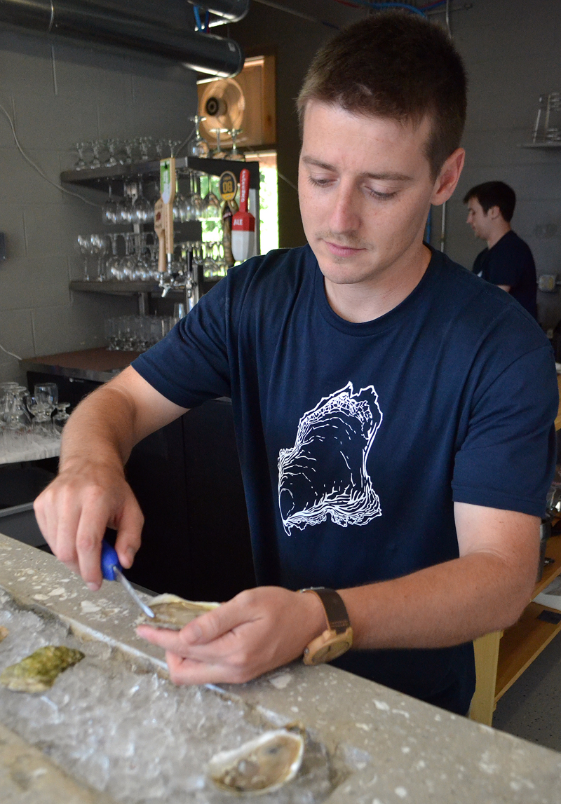 River Bottom Raw Bar owner Brendan Parsons shucks an oyster during the business's soft opening Sunday, Aug. 13. (Maia Zewert photo)