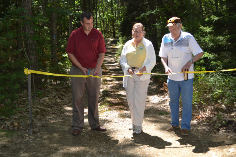 From left: David Seavey, Carrie Kinne, and George Richardson cut the ribbon at the Carl and Barbara Segerstrom Preserve at Squam Creek on Sunday, Aug. 6. The preserve on Westport Island is now open to the public. (Charlotte Boynton Photo)