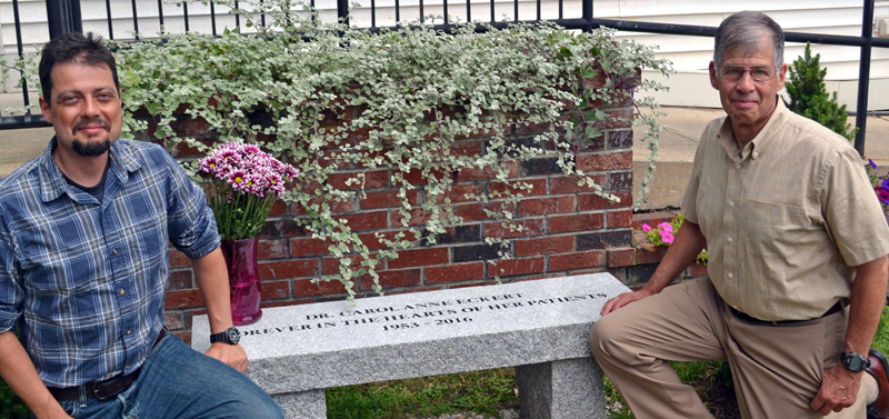 The late Dr. Carol Eckert's son, Sam Frankel (left), and husband, Jeff Frankel, kneel on either side of a bench the Sheepscot Valley Health Center dedicated to her memory Tuesday, Aug. 15. (Abigail Adams photo)