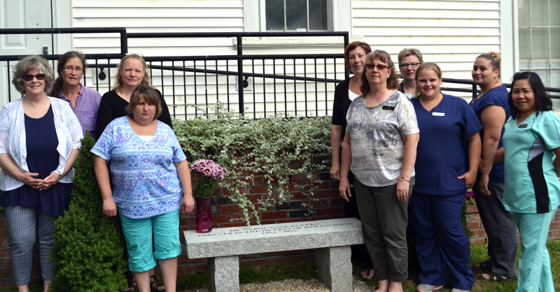 Sheepscot Valley Health Center staff members stand around Carol's Bench, which was dedicated to the memory of Dr. Carol Anne Eckert on Tuesday, Aug. 15. The bench will serve as a peaceful place for staff to sit and enjoy the outdoors. (Abigail Adams photo)