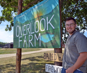 Ridge Barnes stands next to the sign for Overlook Farm. Barnes is the fifth generation of the Barnes family to run the farm. (Charlotte Boynton photo)