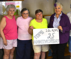 From left: TOPS 206 members Pam Wakelin, Shirley Rice, Virginia Wright, June Caton, Carol Verille, and Ernestine Lincoln hold a sign commemorating the group's 25th anniversary. (Abigail Adams photo)