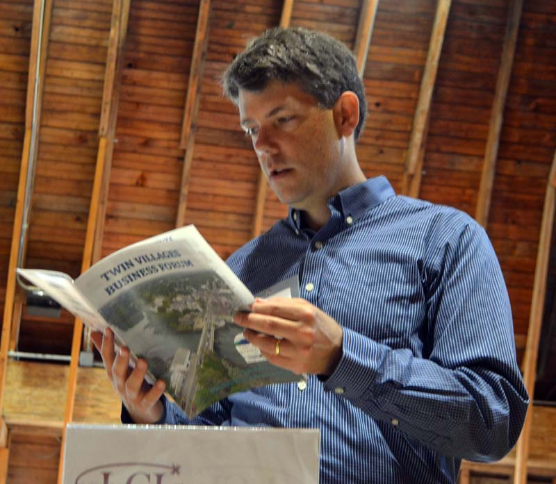 Damariscotta River Association Executive Director Steven Hufnagel looks at a Twin Villages Business Forum program during the forum in the Darrows Barn at Round Top Farm on Friday, Sept. 22. (Maia Zewert photo)
