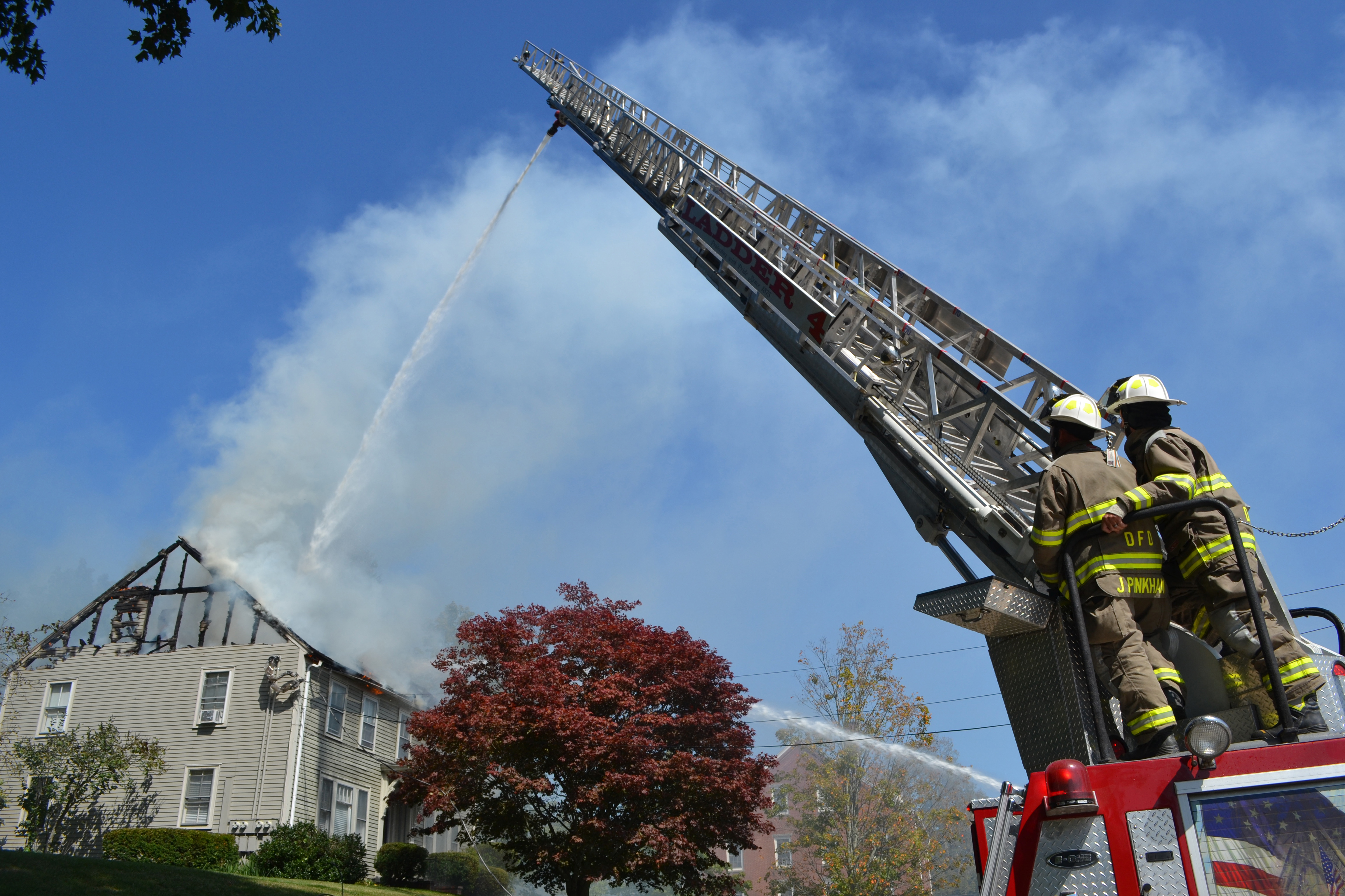 Damariscotta firefighters Josh Pinkham (left) and Jim Hall use their department's ladder truck to fight a fire at 50 Main St. in Newcastle on Tuesday, Sept. 12. (Maia Zewert photo)