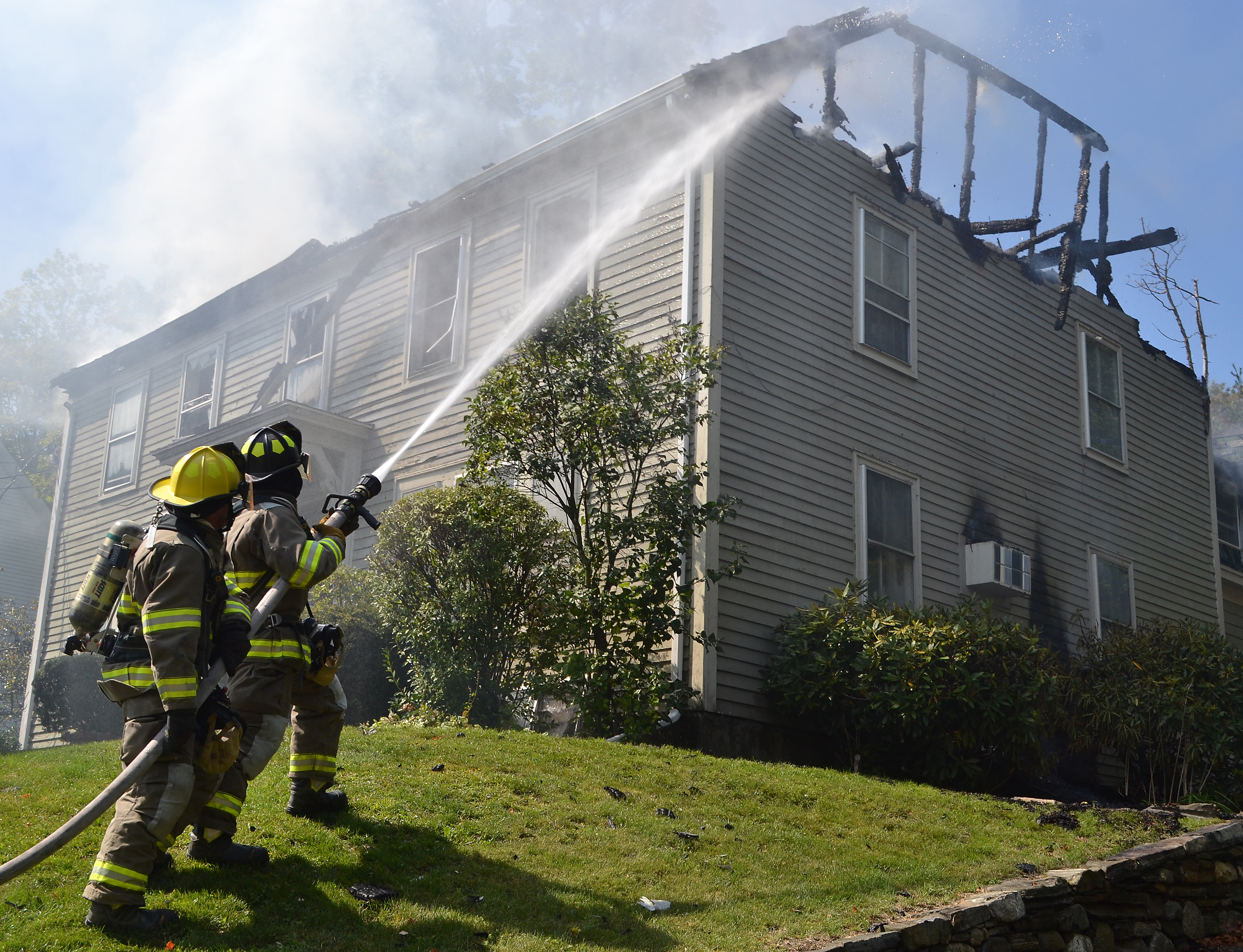 Firefighters douse hot spots in the remains of the roof at 50 Main St. in Newcastle. (Maia Zewert photo)