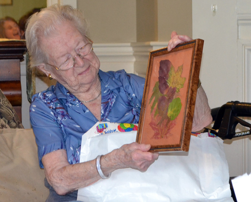 "Elizabeth ""Betty"" Pierce admires a gift during her 100th birthday party at Chase Point Assisted Living in Damariscotta on Sept. 26. (Charlotte Boynton photo)"