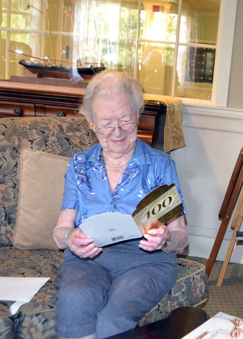 "The county's newest centenarian, Elizabeth ""Betty"" Pierce, smiles as she reads a 100th birthday card from the staff of the Westport Island town office. (Charlotte Boynton photo)"
