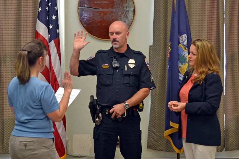 Wiscasset Town Clerk Linda Perry (left) administers the oath of office to Wiscasset Police Department Sgt. Craig Worster on Monday, Sept. 11 as Worster's fiancee, Dr. Margaret Marcone, looks on. (Abigail Adams photo)