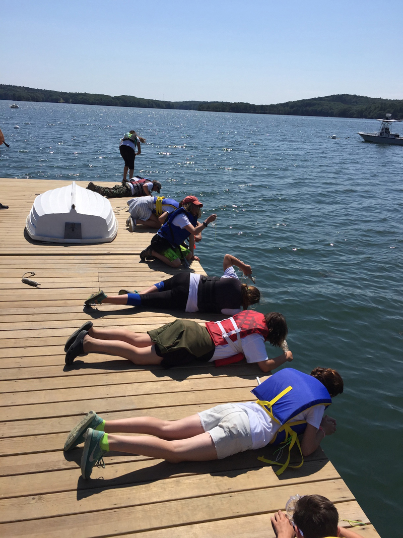 Boothbay Sea and Science Center campers take temperature, salinity and turbidity measurements with thermometers, hydrometers, and Secchi disks off the Darling Marine Center dock.