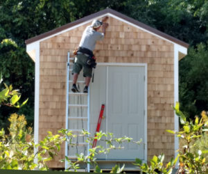 Peter Hallett nails the final shingle in place on the Ecumenical Diaper Bank's new storage house.