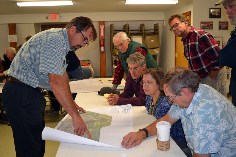 Crooker Construction's recently hired environmental coordinator, Michael Abbott (left), shows a map of proposed Bailey Road changes to attendees of an Oct. 3 informational meeting in Alna. (Christine LaPado-Breglia photo)
