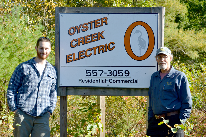 Daniel Baty (left) and Al Monaco stand in front of the sign for Oyster Creek Electric at 629 Bristol Road. Monaco is selling the business to Baty, his employee of four years. (Maia Zewert photo)