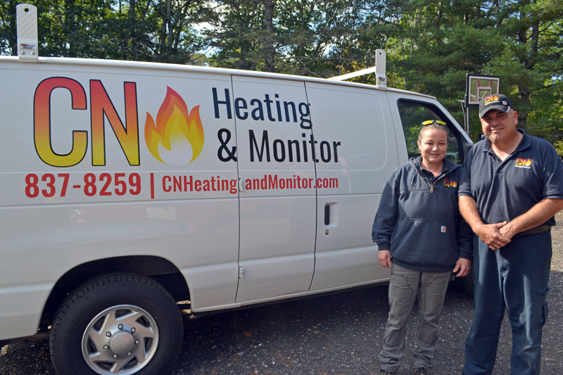 Caitlin Pinkerton and Nick Falabella, the partners behind CN Heating & Monitor, stand next to the company van at their headquarters in Round Pond. (Maia Zewert photo)