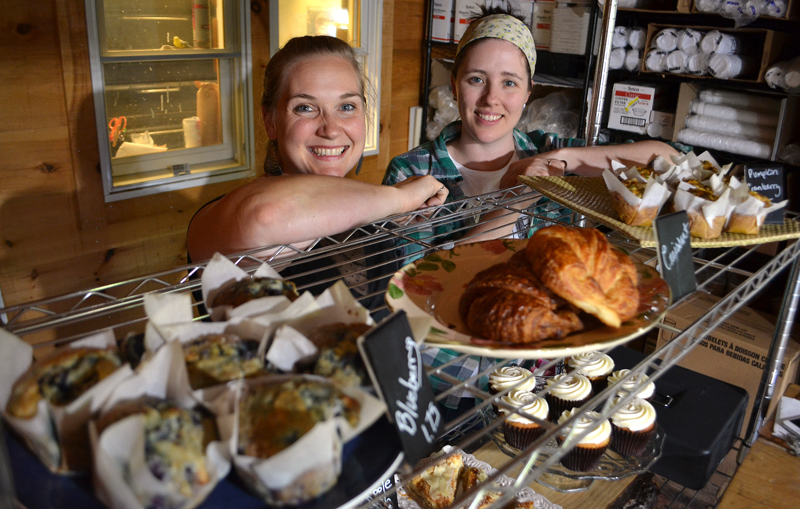 """Longtime friends Crystal Berg (left) and Andrea """"Annie"""" Leck stand behind a collection of Barn Door Baking Co. offerings Saturday, Oct. 14, the first of the business's open bakery days. (Maia Zewert photo)"""