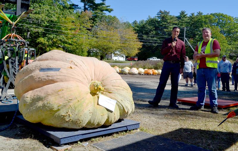 Charlie Lopresti (left) and Joseph Gaboury await the weight reveal of Gaboury's pumpkin during the Damariscotta Pumpkinfest's annual giant pumpkin weigh-off at Pinkham's Plantation on Sunday, Oct. 1. (Maia Zewert photo)
