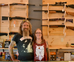 Dresden Take Out owners Mason and Kathy Dubord stand in front of a rack of firearms in the store's new gun room Tuesday, Oct. 10. (Maia Zewert photo)
