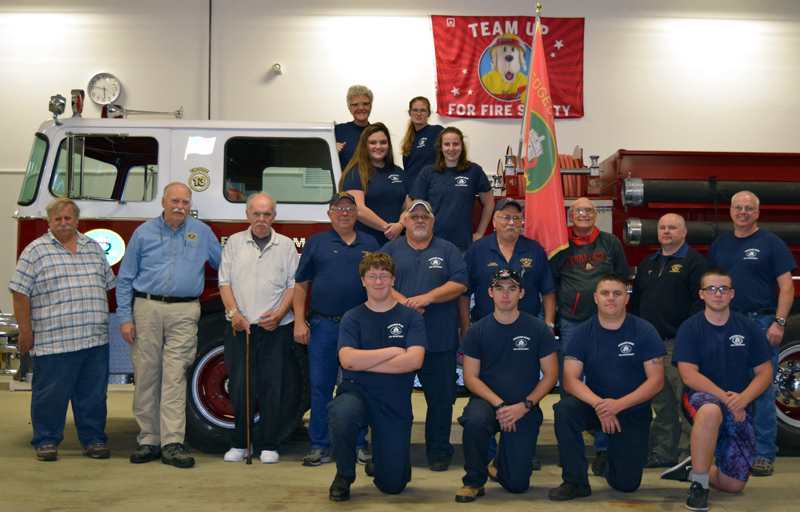 Edgecomb Fire Department members past and present pose for a photo at the fire station Thursday, Oct. 5. Front row from left: Aidan Tracey, Josh Kramley, Marc Babineau, and Ryan Potter. Middle: former Chief Barry Johnston, former Assistant Chief Larry Omland, Capt. Steve Fenton, Bill Witzell, Lt. Roland Abbott, Lt. Daren Graves, Capt. Tom Trowbridge, Assistant Chief John Potter, and Chief Roy Potter. Bottom row on truck: Ryann Trask and Leah Potter. Top row: Chaplain Kate Pinkham and Amanda Babineau. (J.W. Oliver photo)