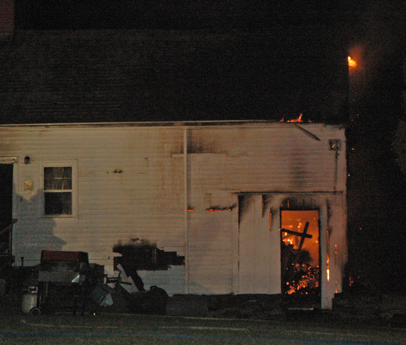 Flames are visible in a shed-like structure attached to the house. The fire started in the shed and spread to the main house. (Alexander Violo photo)