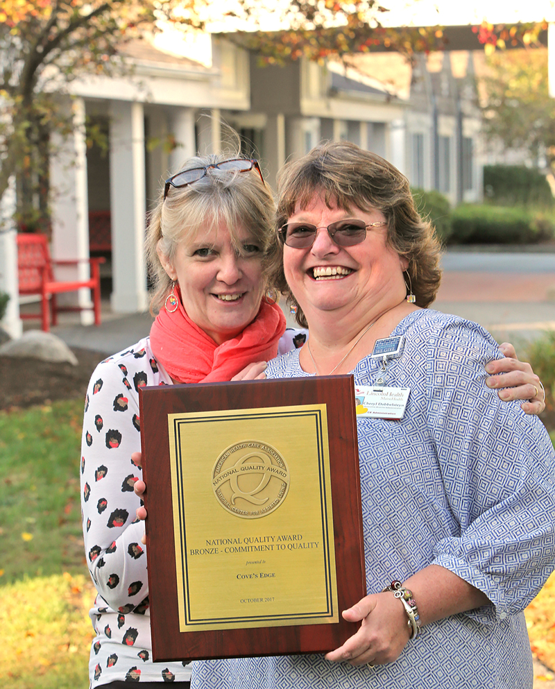 Cove's Edge Director of Nursing Thelma Hannan (right) holds the 2017 Bronze Commitment to Quality Award as Cove's Edge Executive Director Cheryl Dobbelsteyn looks on.