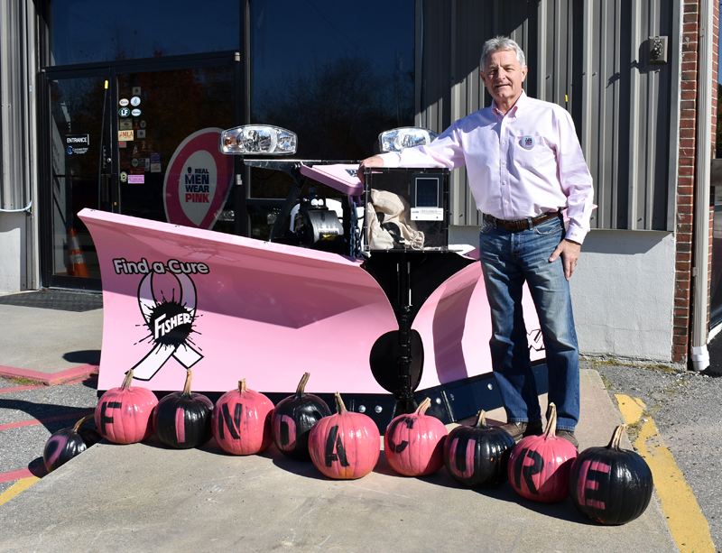Randy Miller of Newcastle Chrysler Dodge Jeep Ram Viper stands at his dealership with a pink plow he is auctioning off.