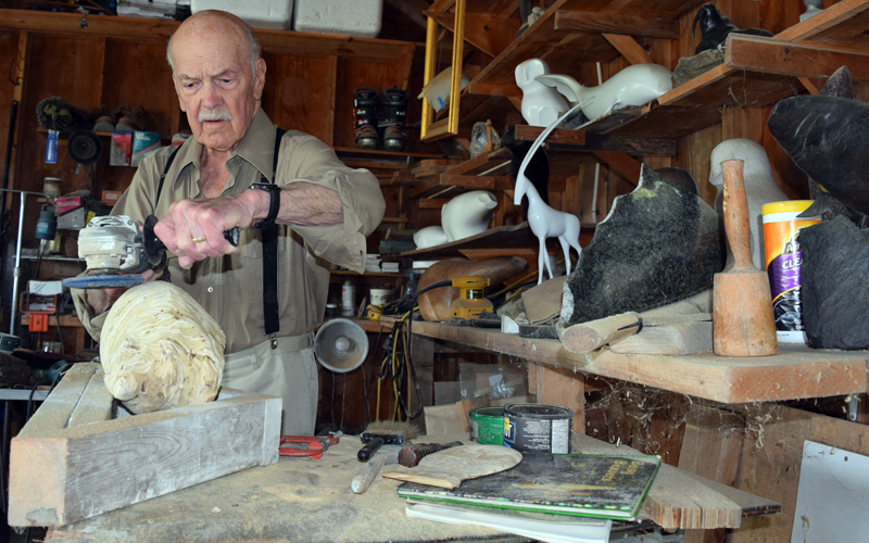 Ralph Moxcey uses an electric grinder to shape a wooden beaver sculpture in his Bremen garage. Some of his previous sculptures are on the shelves beside him. (J.W. Oliver photo)