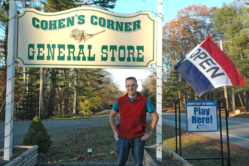 Ronald Cohen stands in front of the sign for Cohen's Corner General Store, now open on Route 27 in Edgecomb. (Alexander Violo photo)