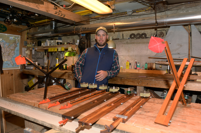 Oliver Butler in his Damariscotta Mills workshop with a variety of his ice fishing traps, including a cross trap made with ebony (left). (Paula Roberts photo)