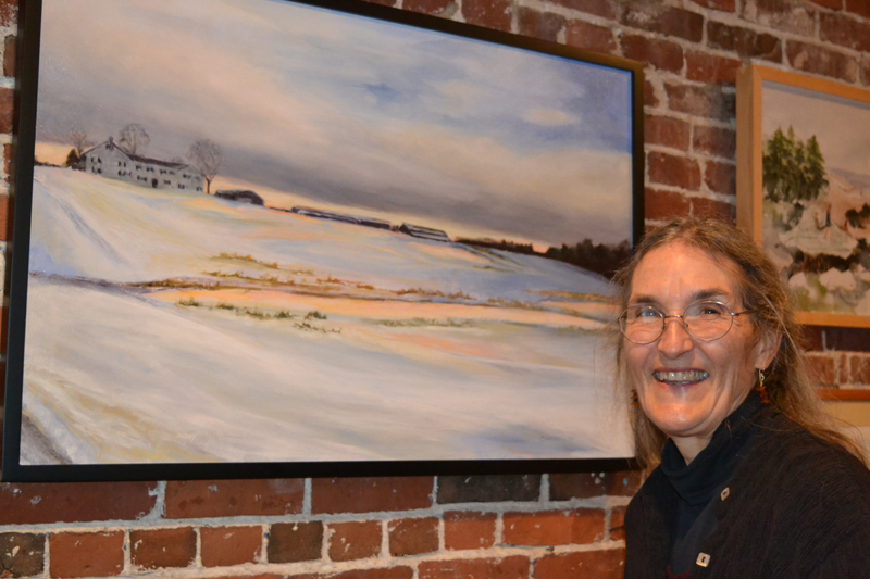 "Artist Susan Parrish Carter poses next to ""Spring Brook,"" her glazed oil-on-canvas painting currently on exhibit at Damariscotta River Grill. (Christine LaPado-Breglia photo)"