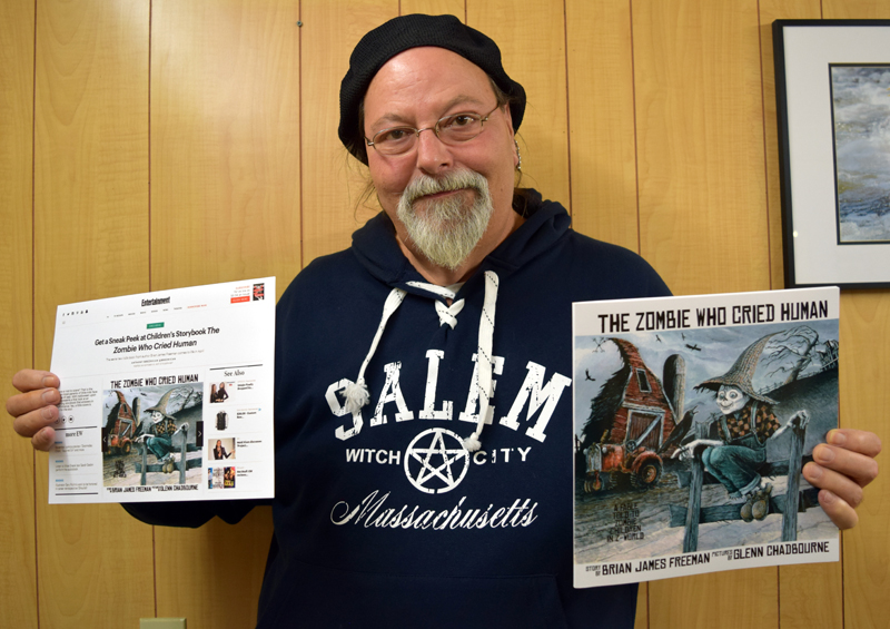 "Newcastle artist Glenn Chadbourne holds a print-out of an Entertainment Weekly post about his forthcoming book (left) and an advance copy of the book, ""The Zombie Who Cried Human."""