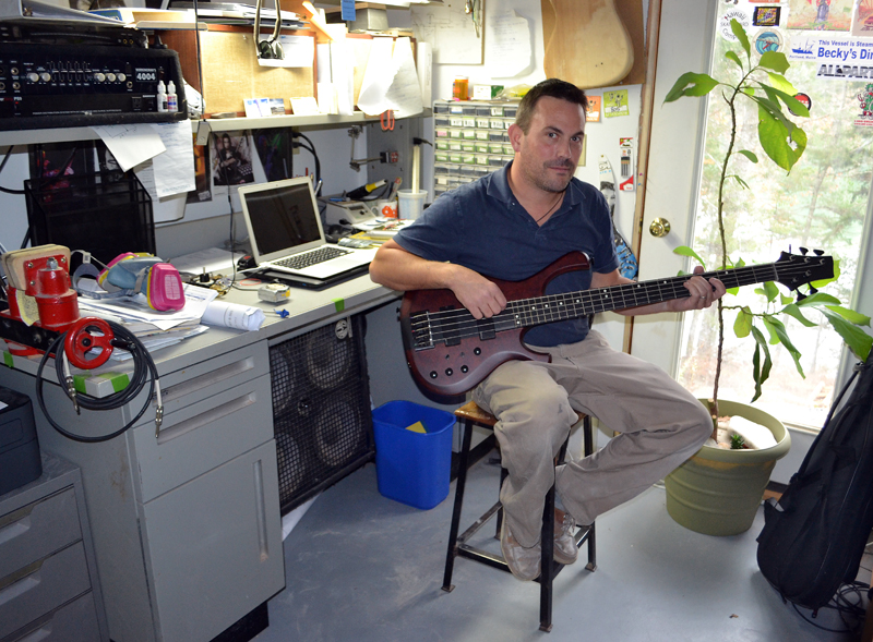 Jonathan Kelsey holds one of the guitars he built at JK Custom Woodworking in South Bristol. (Maia Zewert photo)
