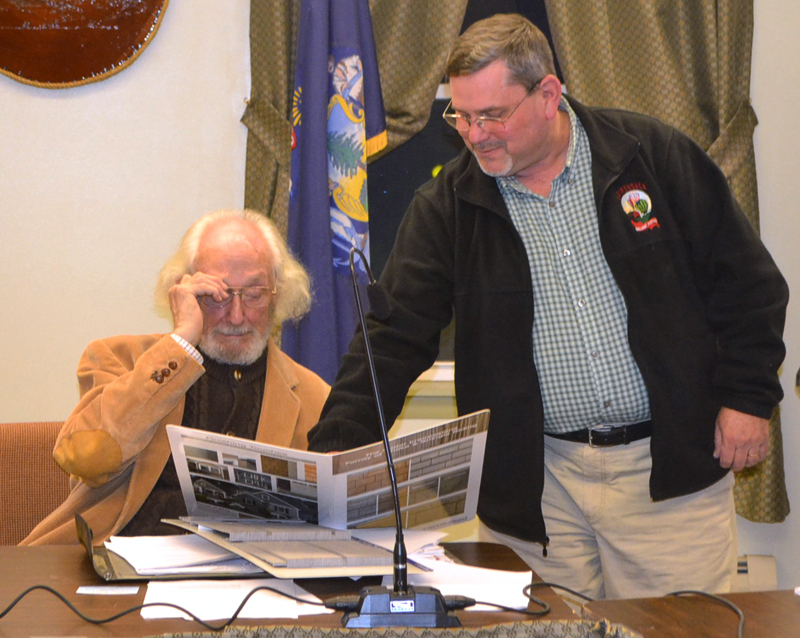 Charles Applebee (standing) shows Wiscasset Historic Preservation Commission Chair John Reinhardt the materials he will use in the renovation of the former Wiscasset Newspaper office. (Charlotte Boynton photo)