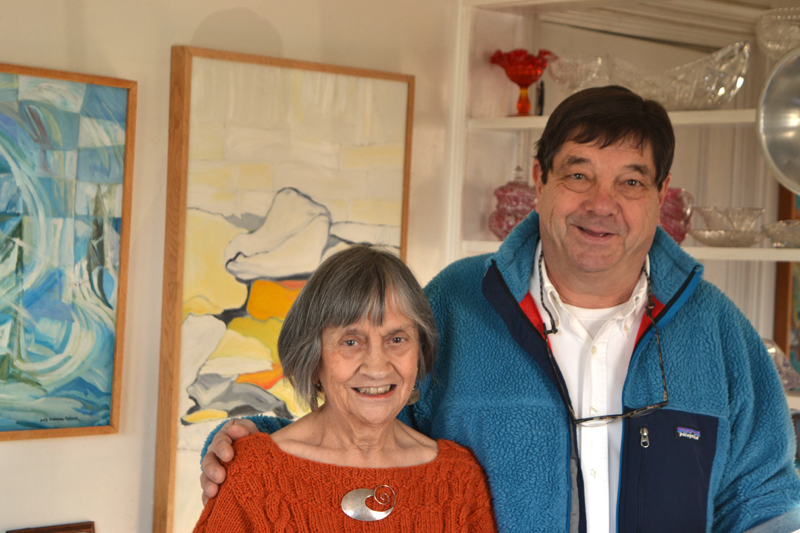 """Round Pond artist Sally DeLorme Pedrick and gallery visitor Mark DesMeules stand before Pedrick's paintings """"A Season of Chess"""" (left) and """"North Wall"""" on Sunday, Dec. 3. (Christine LaPado-Breglia photo)"""