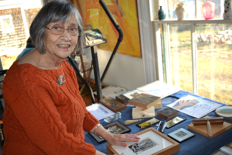 Sally DeLorme Pedrick, who creates woodcuts in addition to painting and blowing glass, talks about her woodcut process at a Dec. 3 opening reception at her home gallery, The Library Art Studio in Round Pond. (Christine LaPado-Breglia photo)