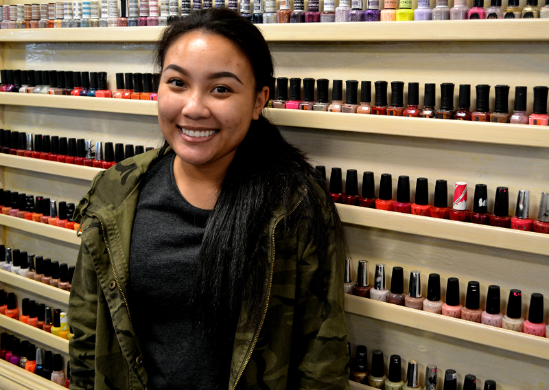 Mainely Nails owner Mary Huynh stands in front of a rack of nail polish in the salon's new location at 523 Main St. in Damariscotta. (Maia Zewert photo)