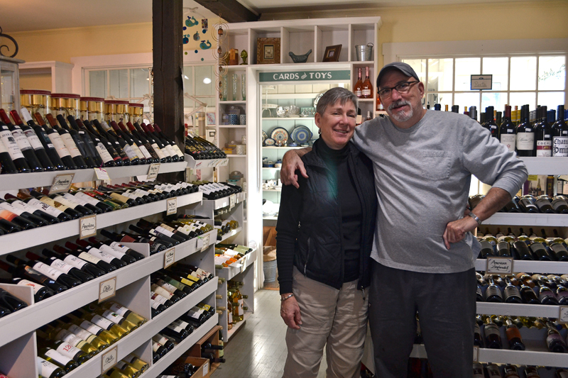 Weatherbird owners Debra and Scott Devlin stand in the specialty food store's wine section. The Devlins recently purchased the food and kitchenware shop from Wayne and Joanne Moore, who will continue to own the clothing store on Main Street now known as W Boutique. (Maia Zewert photo)