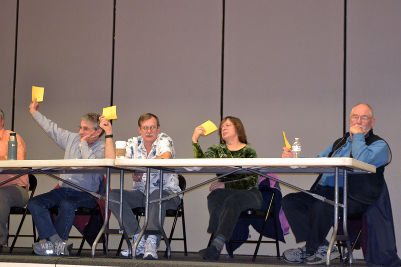 From left: Whitefield Selectmen Tony Marple, Lester Sheaffer, Charlene Donahue, and Frank Ober raise their cards to vote for a 180-day moratorium on marijuana establishments during a special town meeting at Whitefield Elementary School on Wednesday, Dec. 6. (Christine LaPado-Breglia photo)
