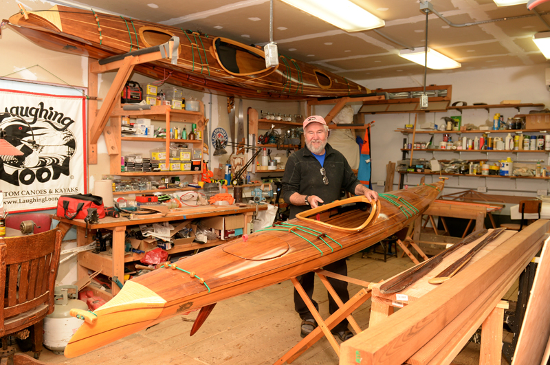 Rob Macks easily lifts a 28-pound kayak he made in his Laughing Loon workshop in Jefferson. (Paula Roberts photo)