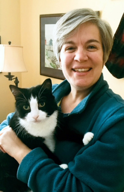 Trendy Stanchfield poses with her newest family member, Ermie the tuxedo cat, recently adopted from Coastal Humane Society. Stanchfield will serve as the organization's new executive director starting Tuesday, Jan. 2.