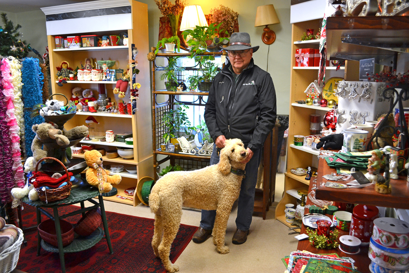 Guy Thompson, owner of First Class Florals and All the Comforts, stands in the middle of the store with his dog, Jessy. The store will close Friday, Jan. 5. (Maia Zewert photo)
