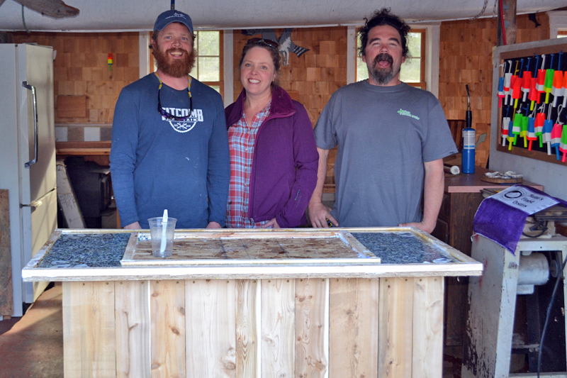 From left: Chase Morrill, Ashley Morrill-Eldridge, and Ryan Eldridge stand in front of a mobile shucking station built for a renovated cabin at Glidden Point Oyster Farm in Edgecomb. (LCN file photo)