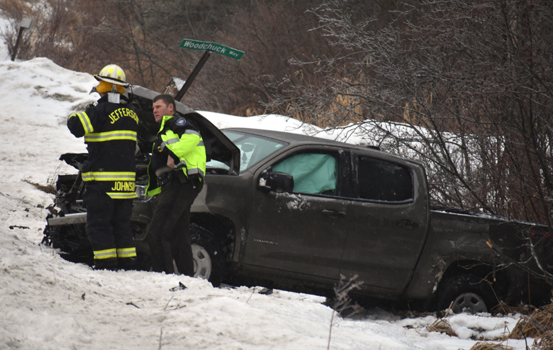 A Jefferson firefighter and Lincoln County Sheriff's Deputy Kevin Dennison work at the scene of a single-vehicle accident on Route 32 in Jefferson on Tuesday, Jan. 23. (Alexander Violo photo)