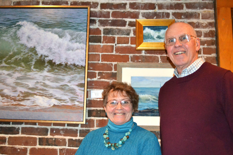 "Artists Cindy Spencer and Bob Vaughan enjoy the Jan. 24 opening reception for the Pemaquid Group of Artists show at Damariscotta River Grill. Behind them are Will Kefauver's painting ""Big Wave"" (left), Sally Loughridge's ""Breaker"" (top right), and Kay Sawyer Hannah's ""Sails Out 'n Away."" (Christine LaPado-Breglia photo)"