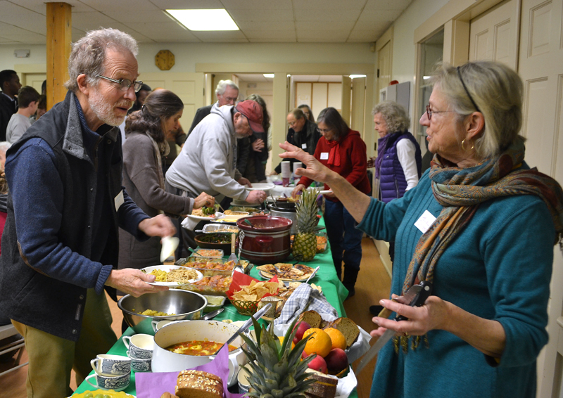 Neighbors George Mason and Paula Christensen, of Nobleboro, greet each other during a potluck at The Second Congregational Church in Newcastle on Martin Luther King Jr. Day. (Maia Zewert photo)