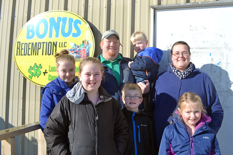 The Stevens family recently purchased Bonus Redemption LLC, which operates redemption centers in Damariscotta and Newcastle. From left: Elle , Emme, Casey, Nelsen, Reuben, Erica, and Brayelyne Stevens. (Maia Zewert photo)