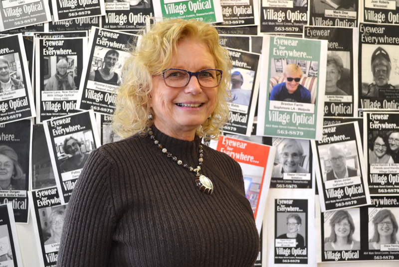 Village Optical owner Jane Hall stands in front of a wall of her clients' photos in the business at Main Street Centre in Damariscotta. The business will close March 31 after 29 years. (Maia Zewert photo)