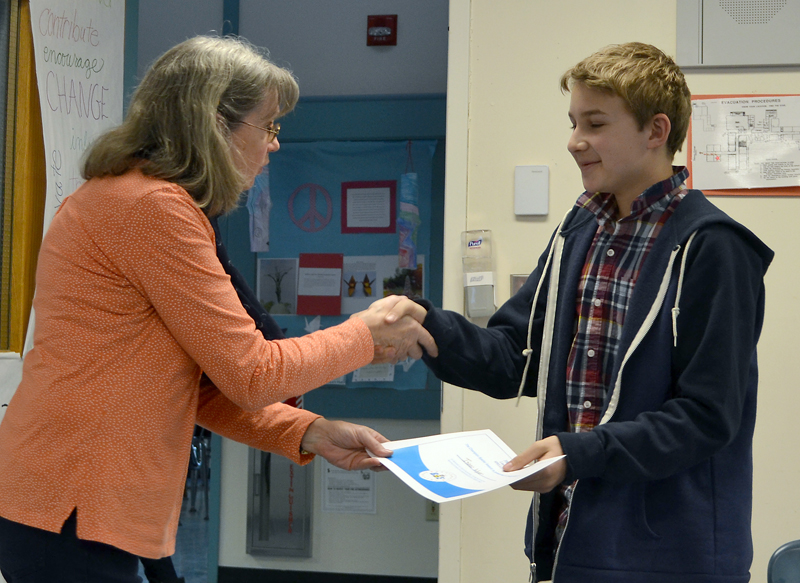Lincoln County Spelling Bee moderator and Bristol Consolidated School teacher Becky Cooper presents Isaac Wyer with a certificate for winning the bee Thursday, Feb. 8. (Maia Zewert photo)