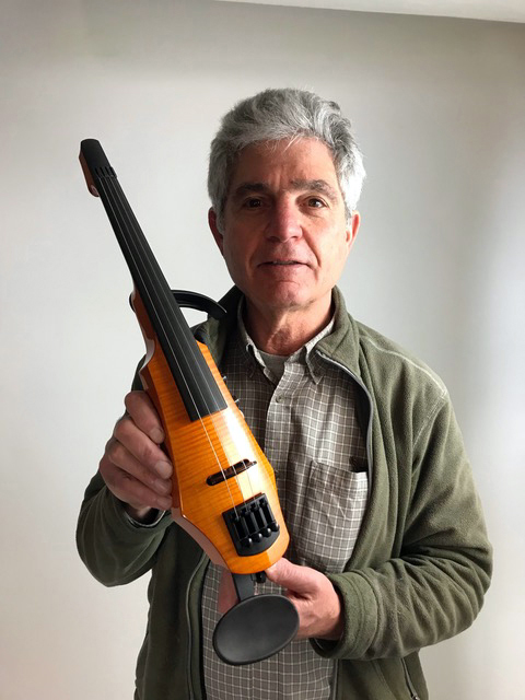 Designer Ned Steinberger holds the NS Designs WAV4 electric violin he has donated for the auction.