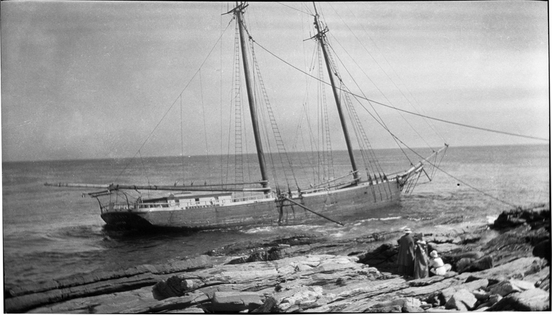 "Women look at the two-masted schooner ""Willis and Guy"" that wrecked on the rocks of Pemaquid Point on Aug. 17, 1917. The original negative of this image was shared with the Old Bristol Historical Society's digital images archive by Mollie Perley."